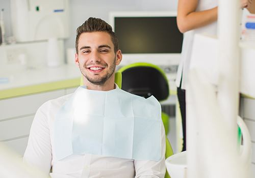 Man smiling in dental chair after dental checkup