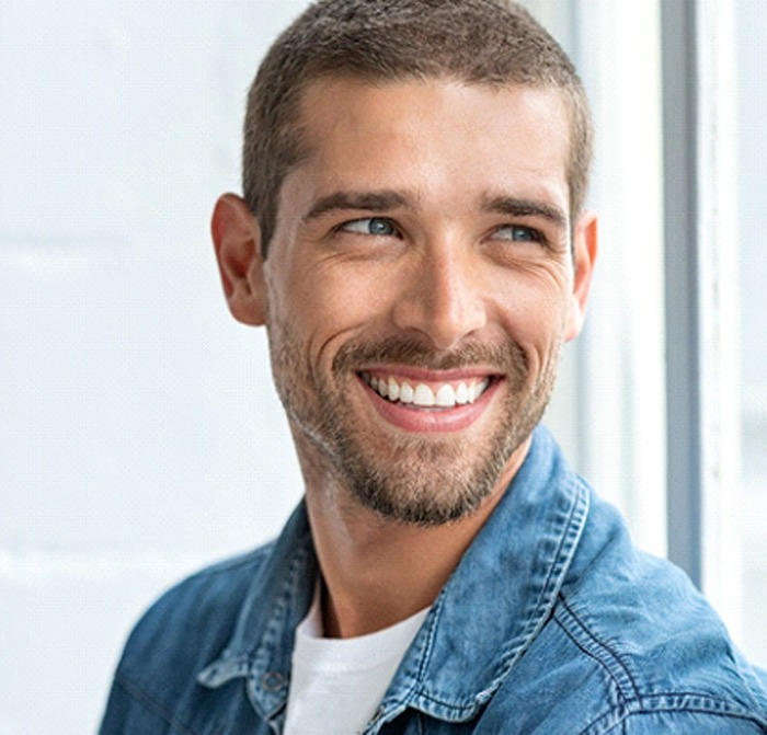 Smiling, handsome man happy with cost of dental implants Kerrville