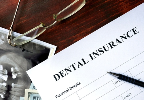 Dental insurance form on table next to X-ray and glasses