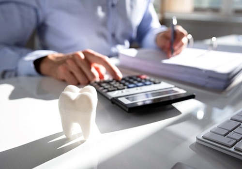 Man at desk, calculating cost of dental treatment