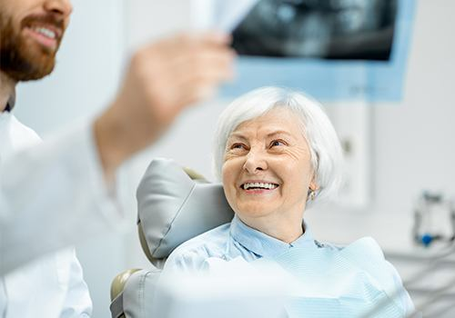 Older woman talking about dentures with her dentist