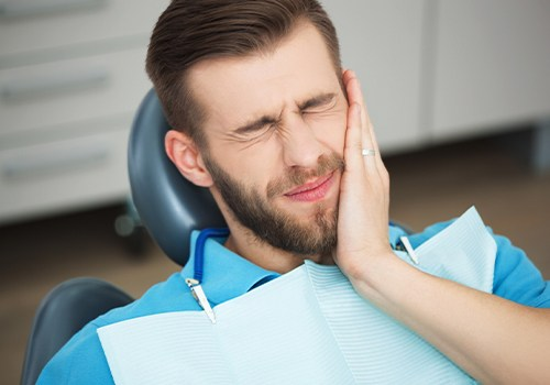 Man in need of wisdom tooth extraction holding jaw