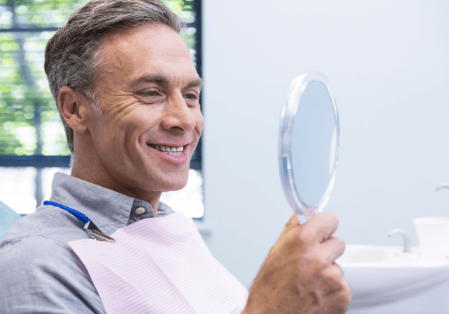 Man looking at smile in mirror after dental implant tooth replacement
