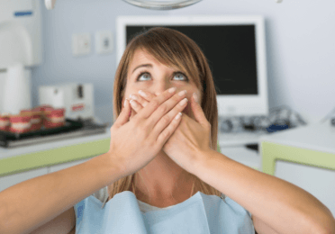 Fearful patient in need of sedation dentistry covering her mouth