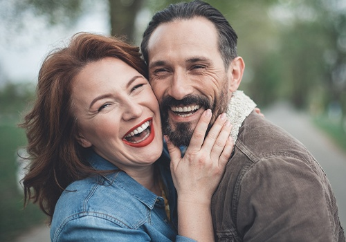 Man and woman showing off beautiful smiles after porcelain veneers